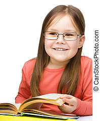 Little girl is reading a book - Cute little girl is reading...