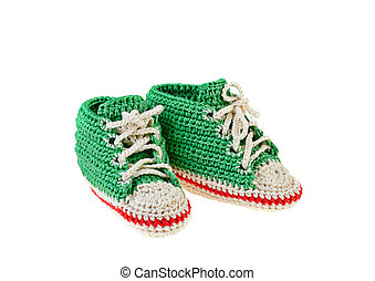 Green crochet baby booties with red line isolated on white