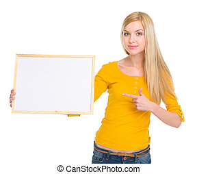 Happy student girl pointing on blank board