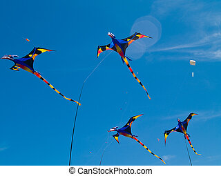 Various Colorful Pterodactyl Kites Flying in a Bright Blue...