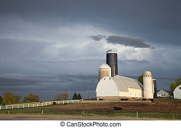 Barn and silos of midwestern farm under stormy skies - A...