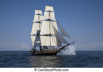 Tall ship with cannons firing sailing on blue waters - A...