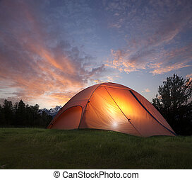 Tent with light inside at dusk near the Grand Teton...