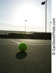 Backlit Tennis Ball with Practice taking place in the...