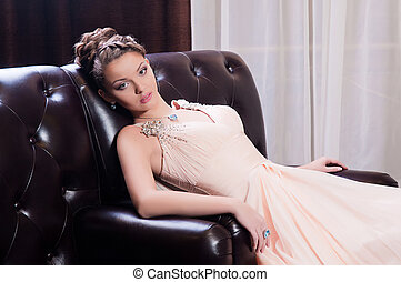 woman in a long sitting on the couch