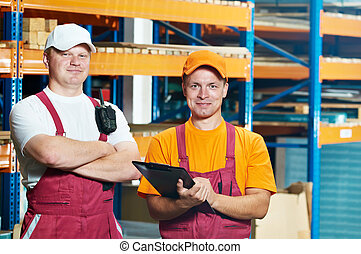 manual workers in warehouse - two young warehouse workers...