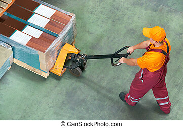 worker with fork pallet truck stacker in warehouse loading...