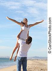 Man on the beach raising his girlfriend