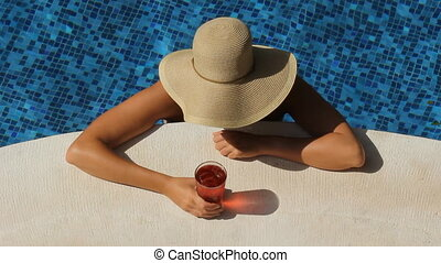 Drink by the pool - Woman with wide brimmed hat by side of...