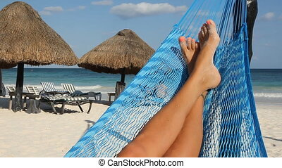 Hammock feet. Wide shot. - Feet up in a hammock with palapas...