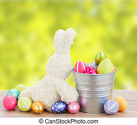 egg hunt - easter rabbit with metal pot full of eggs in...