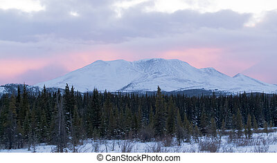 Sunset glow behind winterly Little Peak YT Canada - Purple...