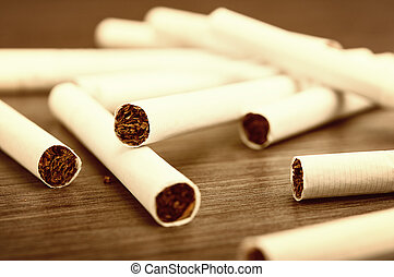 heap of cigarettes and tobacco on a dark wooden background