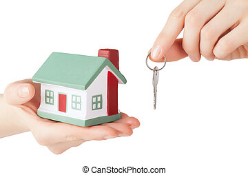 House sale - Little house toy and key in hands isolated over...