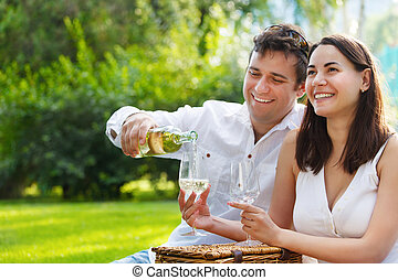 Young happy couple enjoying a glasses of white wine in the...