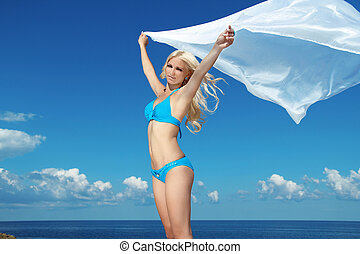 Portrait of young woman feeling free against blue sky with blowing fabric