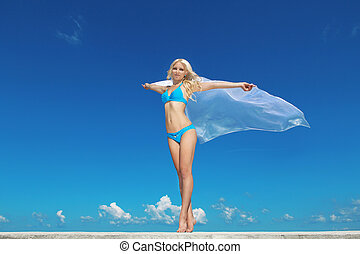 Portrait of young woman feeling free against blue sky with blowing fabric. Freedom Concept