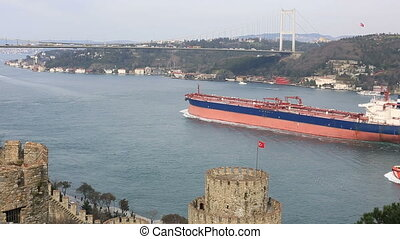 container ship passing under the bridge