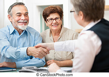 Meeting - senior couple smiling while shaking hand with...