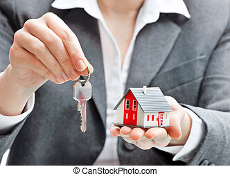 Businesswoman with house model and keys - Real estate agent...
