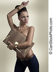 fashion brunette in jeans with big bag and hand on the head...