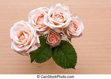 pink roses in a vase on a wooden desk