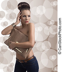 fashion brunette in jeans with big bag and hand near the...