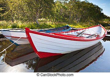 Floating Wooden Boats with Reflection in a Water
