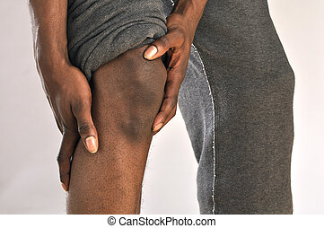 Knee injury - Closeup of African American man clutching...