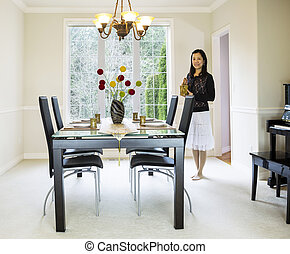 Mature woman holding tea pot in formal dining room