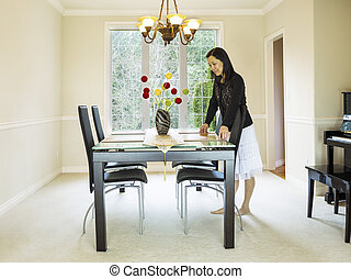 Mature woman preparing dining room table