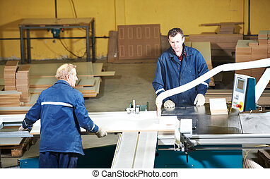 workers at wood processing with circ saw - technician...