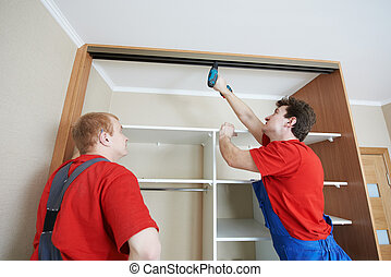 Wardrobe joiners at installation work - Two wardrobe...