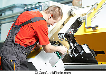 worker operating CNC machine center - mechanical worker of...