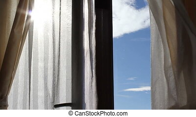 Wind blowing curtains with blue sky in the background
