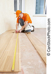 carpenter worker joining parket floor - parquet floor layer...