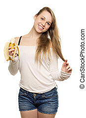 Pretty smiling woman holding banana and touching her blond...
