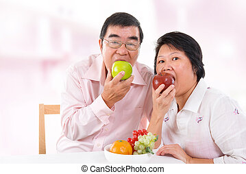 Asian mature couple eating apple - Southeast Asian mature...