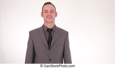 Smiling handsome young businessman standing straightening...