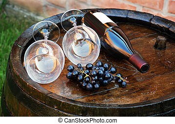 Wood Wine barrel - glasses and bottle of wine lying over...