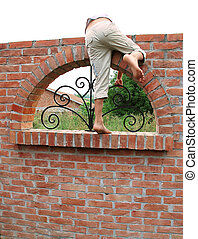 Escape over brick wall - barefooted child climbing on brick...