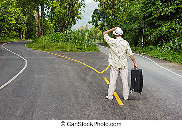 a man with a suitcase is on a fork in the road