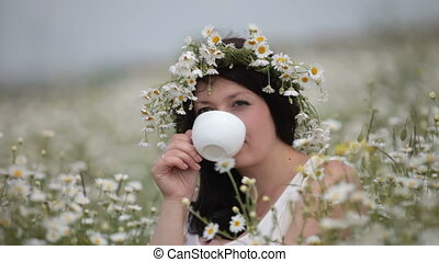 Woman with a cup in the field of daisies
