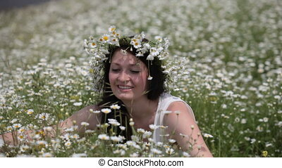 Happy pregnant woman in camomile field
