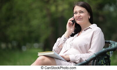 Pregnant woman on the phone - Smiling pregnant woman on the...