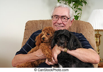 Posing with His Pups - Close-up of a happy senior man posing...