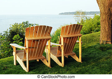 Lake View - Two Adirondack chairs on a hillside overlooking...