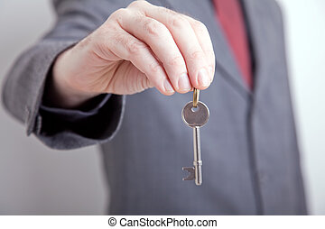 Man in suit holding out key - Landlord/ realtor holding out...
