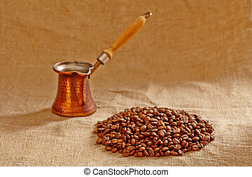 Old copper turkish coffee pot and coffee beans on canvas background. Selective focus