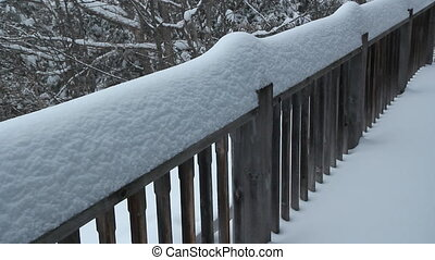 Snowy railing. - Snow falling on a wooden railing during a...